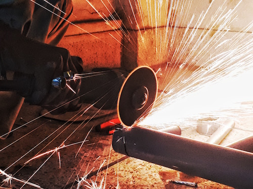 Picture of someone using an angle grinder to cut a pipe