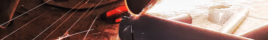 Picture of an angle grinder blade cutting through a metal pipe